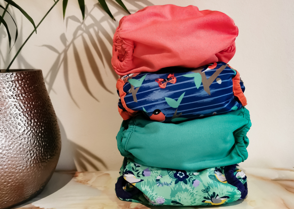 Image shows a stack of 4 brightly coloured Close Pop-in nappies, our first choice cloth nappy for childcare